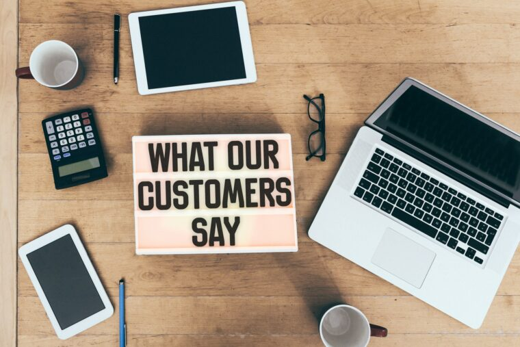 Customer testimonial message on light box at office desk with connected electronic devices